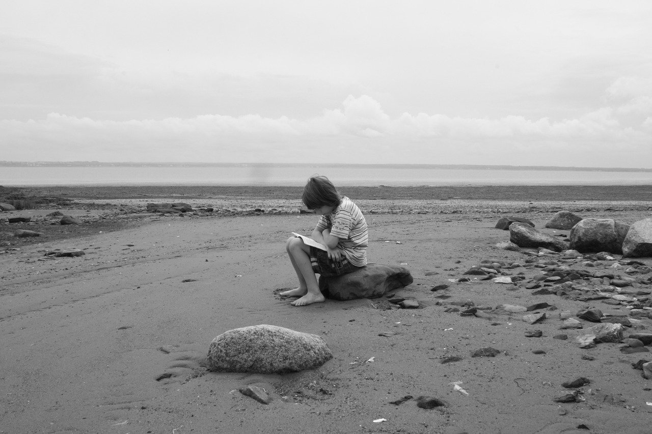 child reading at the beach