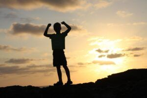 Child with arms raised in victory in sunset