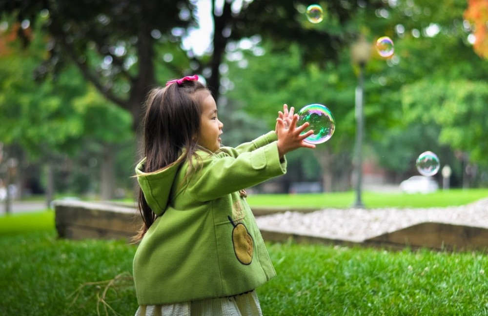 little girl catching bubble in the park
