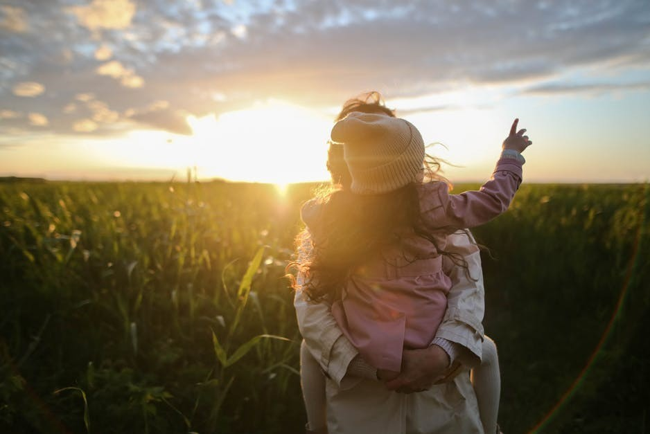 Mom holding daughter in cornfield at sunset