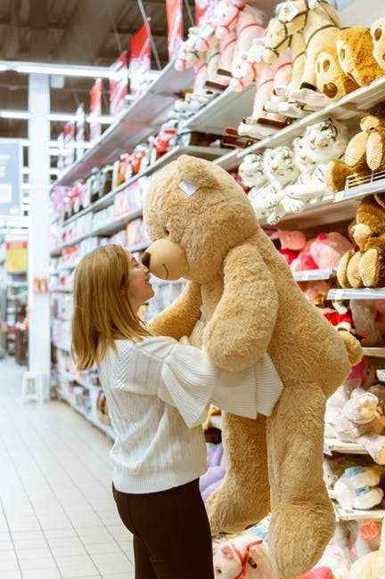 Mom holding huge teddy in toy store