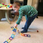 child pulling up magnetic tile construction