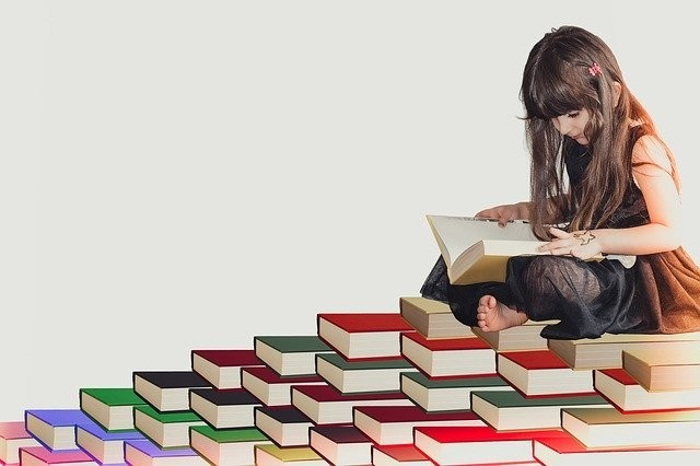 girl reading on a pile of books