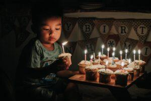 Child holding birthday cupcake with candle