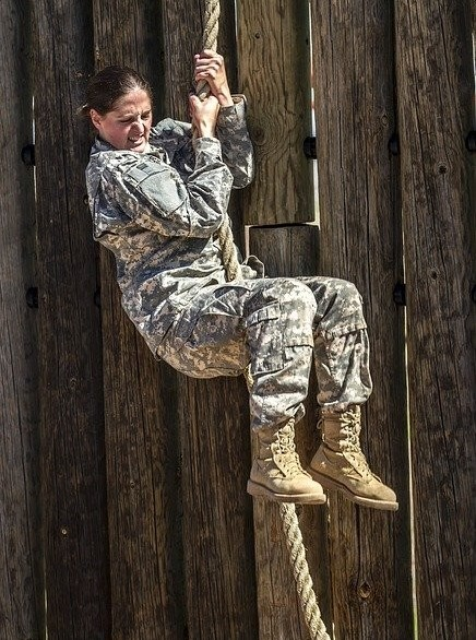 woman in army fatigues climbing the rope