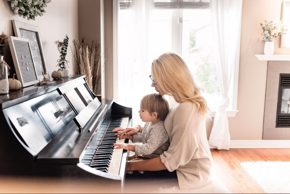 child sitting on mother's lap to practice piano