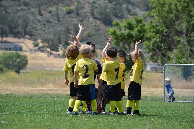 child soccer team raising hands