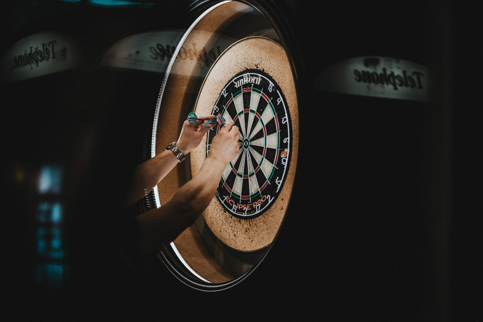 someone removing darts from dartboard