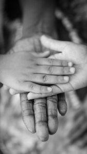 grayscale photo of man, woman, child hands linked