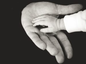 baby's hand in paren's hand, black and white