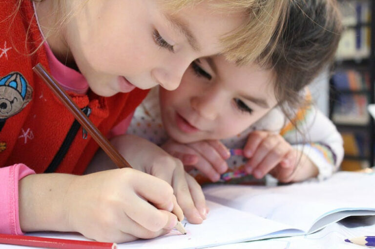 girl writing in book with sister peering over her shoulder