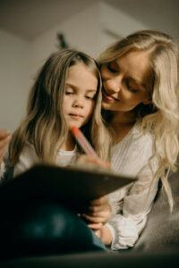 get children writing - little girl writing with her mother